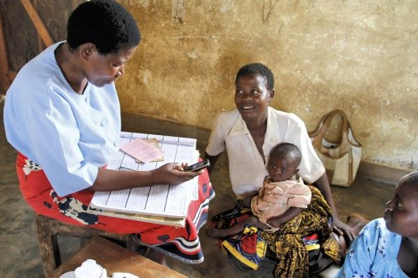 A Community Health Worker in Malawi attends to a sick child using D-Tree's e-protocol on her mobile phone.