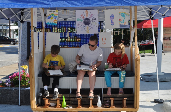 Three people paint on a bench at an outdoors fair.